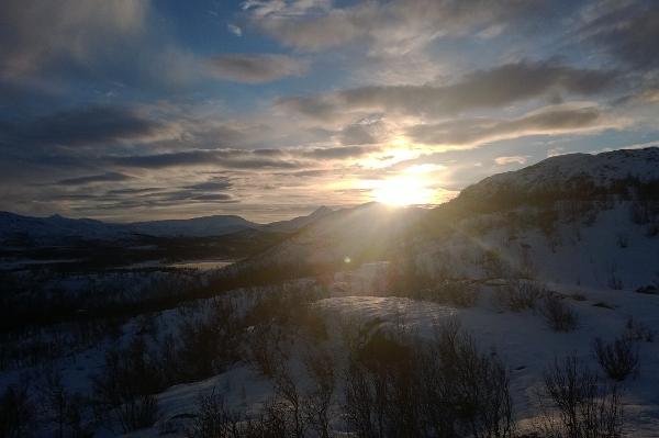 Tromsdalstinden -- like til venstre for sola. Bildet er tatt kl 12.45